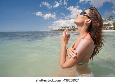 smiling woman in the sea applying protection cream