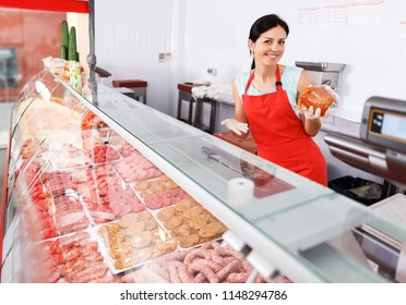 Smiling woman seller showing different sausages in butcher's shop