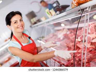 Smiling woman seller showing different meat in butcher's shop