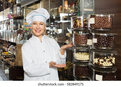 Smiling woman selling chocolates with praline and other fillings