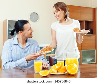 Smiling woman serves croissants and scrambled eggs her beloved man in morning breakfast