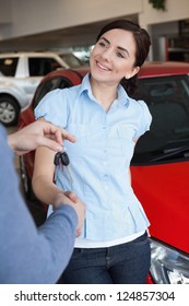 Smiling woman shaking the hand of a man in a car shop