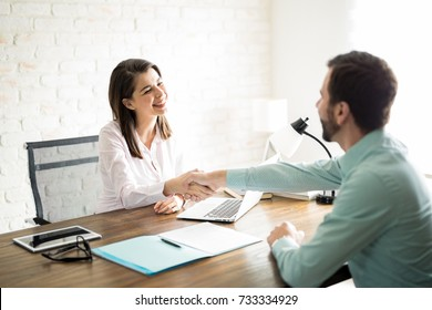 Smiling woman shaking hands with a man she just hired for her office work