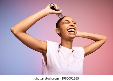 Smiling woman shaving her head. Bold and liberated female cutting her hair with an electric trimmer against multicolored background.
