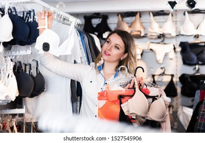 Smiling woman shopper choosing bras in underwear shop