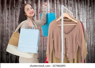 Smiling woman shopping against wooden planks