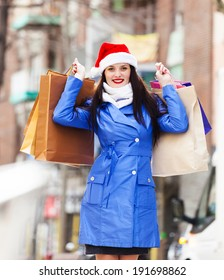 Smiling woman with shopping bags at street during the Christmas sales