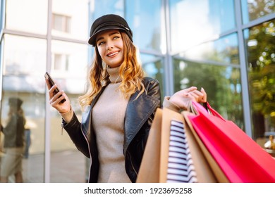 Smiling woman with shopping bags using her phone. Young woman after shopping on the city street. Purchases, black friday, discounts, sale concept. Online shopping concept.