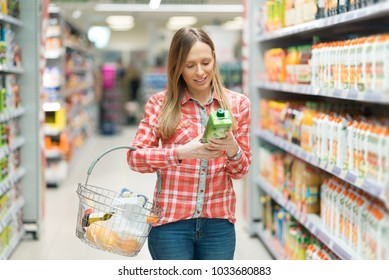 Smiling woman shopping for juice in supermarket