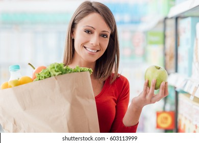 Smiling woman shopping at the supermarket and holding a grocery bag with fresh vegetables, healthy food and lifestyle concept