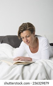 Smiling woman with short hair reading a book in bed