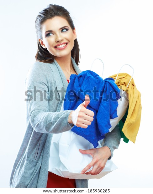 Smiling woman show thumb up. Clothes in shopping bag. Isolated.
