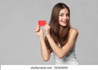 Smiling woman showing blank credit card in white t-shirt, isolated over gray background