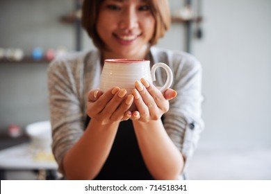 Smiling woman showing clay cup she made in pottery