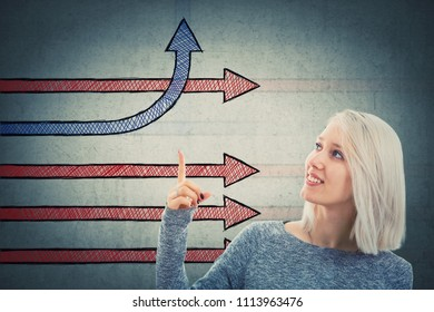 Smiling woman showing imaginative arrows with index finger one change direction bending and going up. Different business thinking, creativity and competition concept, alternative idea. Way to success.