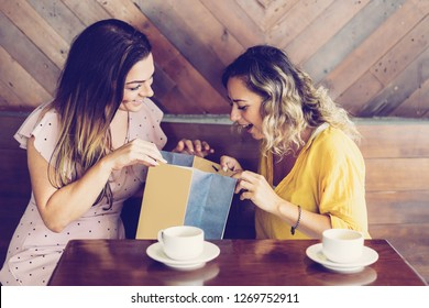 Smiling woman showing purchase to friend in cafe. Ladies drinking coffee and sitting at table. Women friendship and shopping concept.