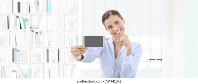 smiling woman showing smart phone in her hand on interior office background