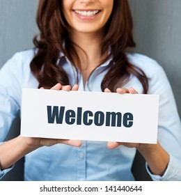 Smiling woman showing white card with welcome word in a close up shot