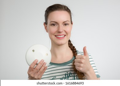 a smiling woman shows a smoke detector and shows thumbs up