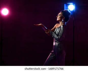 Smiling woman in silver party concert dress overall singer actress is on stage in the club in neon lights holds hand up with open palm for object paste over dark background