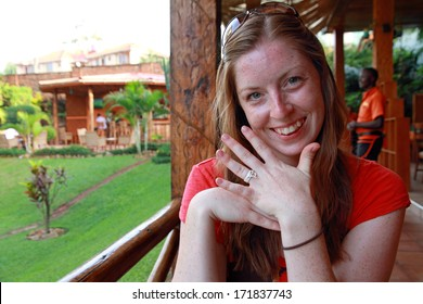 A smiling woman sits in a tropical place displaying her simple and cheap engagement ring made out of string.