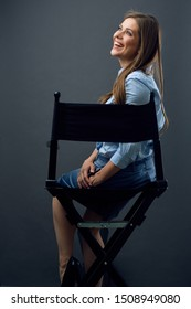 smiling woman sitting back on movies director chair turns away to side. isolated female profile portrait.