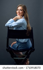 Smiling woman sitting back on chair and looking at camera.