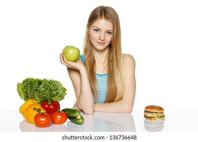 Smiling woman sitting between healthy food and fast food and holding green apple, over white background