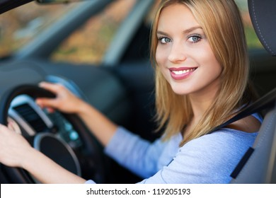 Smiling woman sitting in car