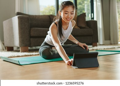 Smiling woman sitting exercise mat and watching training videos on digital tablet. Young chinese female in sportswear exercising watching online videos on tablet pc.