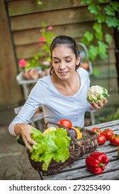Smiling woman sitting at the garden table with a basket of fresh vegetables