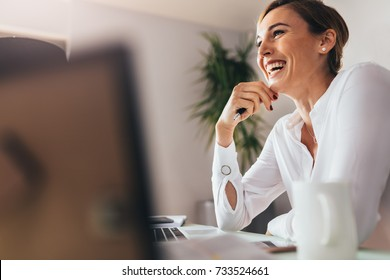 Smiling woman sitting at her desk in office. Happy business woman sitting in office with fingers touching her chin.