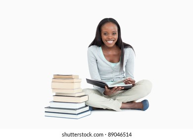Smiling woman sitting next to a pile of books against a white background