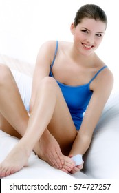 Smiling woman sitting on bed and making pedicure