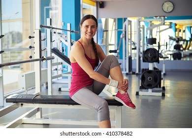 Smiling woman sitting on the bench in gym and put her foot on it