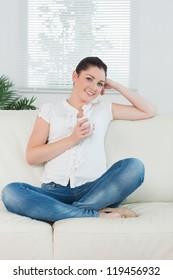 Smiling woman sitting on the couch cross legged and holding a cup of coffee