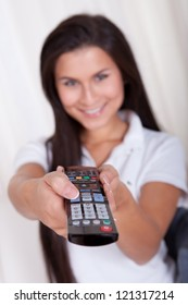 Smiling woman sitting on a couch with a remote control in her hands with copyspace over white curtains