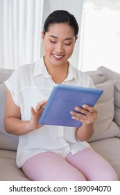Smiling woman sitting on couch using tablet pc at home in the living room