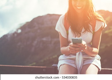 Smiling woman sitting on the fence with mobile phone. High mountains touristic path. Digital communication. Texting with friends in social network