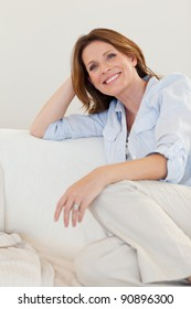 Smiling woman sitting on her sofa