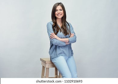 Smiling woman sitting on hi stool. Isolated studio portrait with gray background.