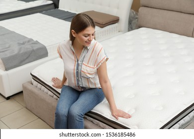 Smiling woman sitting on orthopedic mattress in store