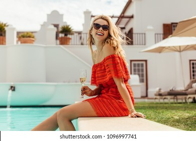 Smiling woman sitting on the pool edge with glass of wine. Beautiful woman relaxing outdoors by swimming pool.