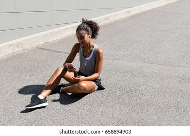 Smiling woman sitting on road, using mobile phone after training