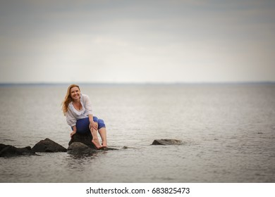 Smiling woman sitting on a rock and looking to the sea