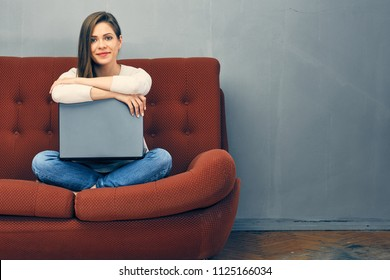 Smiling woman sitting on sofa with open laptop. Woman at home.