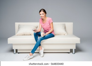 Smiling woman sitting on white couch and using smartphone while drinking coffee isolated on grey