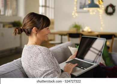 Smiling woman sitting surfing the internet on a laptop computer on a sofa at home, side rear view with the screen with reflections visible