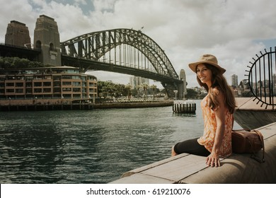 Smiling woman sitting in Sydney in front of Harbour Bridge.