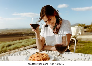 Smiling woman sitting at the table in an open air restaurant with a vineyard in the background. Smiling woman on a wine date sitting with a glass of red wine in hand.